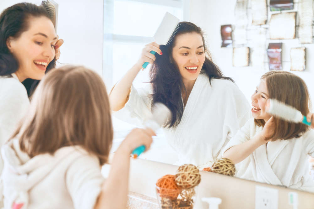 A mother and daughter brush their hair and teeth.