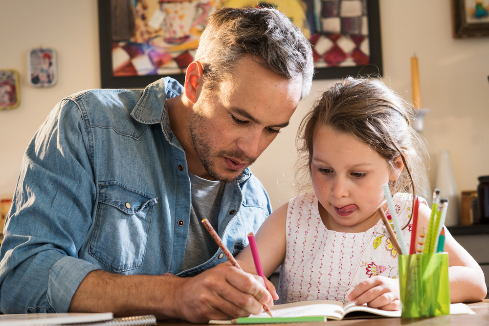 A father helps his young daughter with her homework.