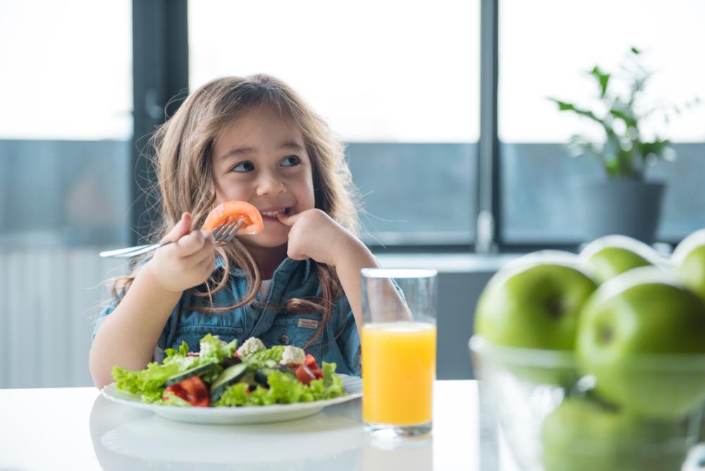 A young girl eats a healthy salad.